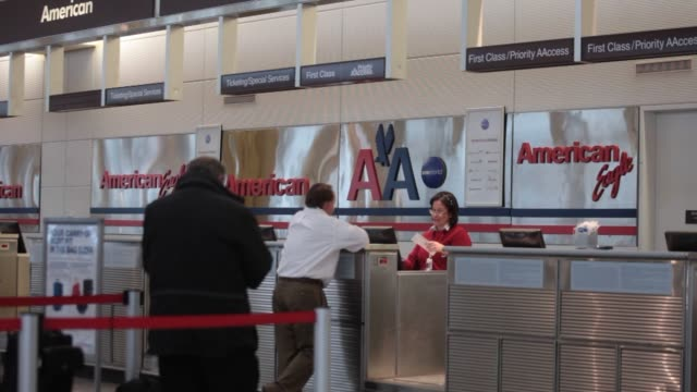 vidéos et rushes de an american airlines group inc employee assists a traveler at the checkin counter at ronald reagan national airport in washington dc us on thursday... - aéroport ronald reagan