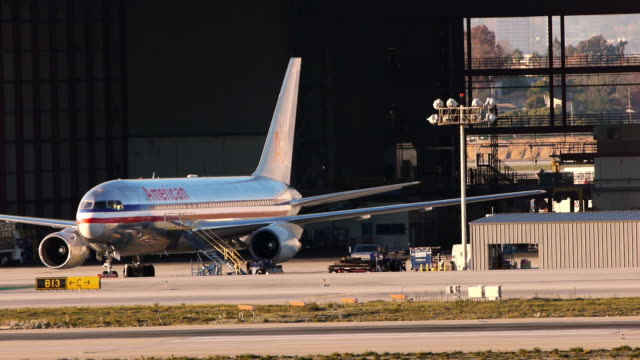 An American Airlines jet parks in a hangar at LAX airport as a small passenger jet taxis by in front.
