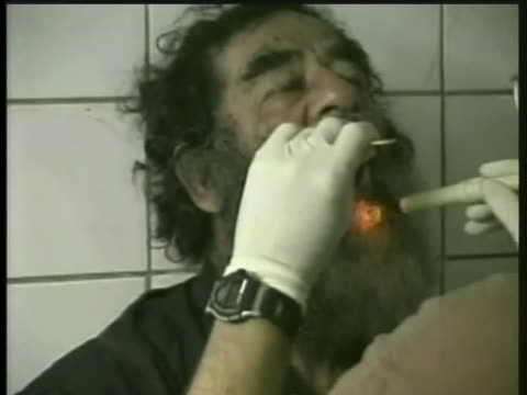 an american army medical worker performs an exam on saddam hussein after his capture - (war or terrorism or election or government or illness or news event or speech or politics or politician or conflict or military or extreme weather or business or economy) and not usa stock videos & royalty-free footage