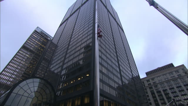 An American flag and a Chicago flag wave in front of Willis Tower in Chicago, Illinois.