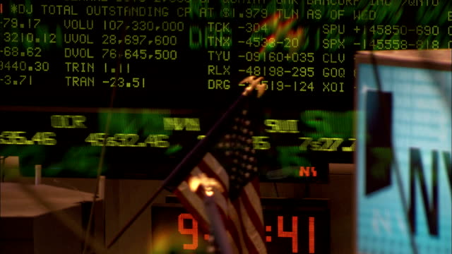 an american flag decorates a stockbroker's desk while the electronic ticker tape displays current stock prices. available in hd. - new york stock exchange stock videos & royalty-free footage
