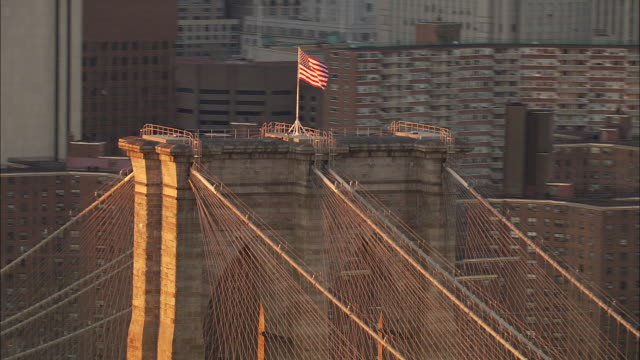 an american flag flies atop the brooklyn bridge. - stars and stripes stock videos & royalty-free footage