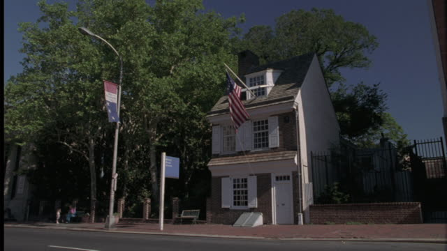 an american flag flies in front of the betsy ross house in philadelphia. - betsy ross house video stock e b–roll