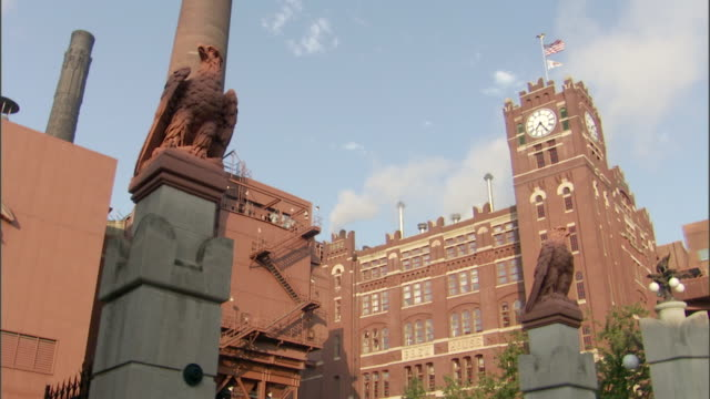 an american flag flies over a clock tower at a budweiser brewery. - turmuhr stock-videos und b-roll-filmmaterial