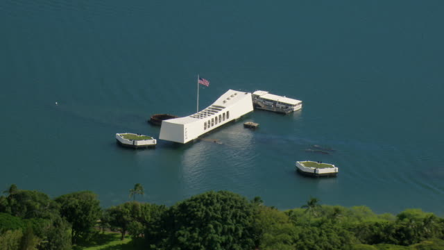 an american flag flies over the pearl harbor memorial in honolulu, oahu. - minnesmärke bildbanksvideor och videomaterial från bakom kulisserna