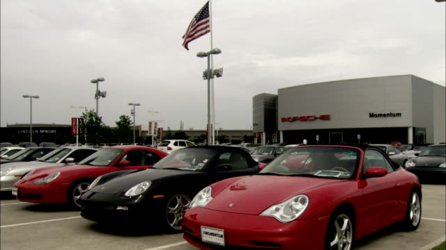 an american flag flutters above the parking lot of a porsche dealership. available in hd. - car showroom stock videos & royalty-free footage