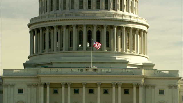 An American flag flutters in front of the dome of the United States Capitol. Available in HD.
