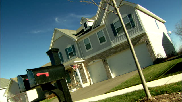 an american flag flutters on the porch of a two-story home. available in hd. - zweistöckiges wohnhaus stock-videos und b-roll-filmmaterial