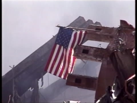 an american flag hangs above the rubble at ground zero in new york. - rubble stock videos & royalty-free footage