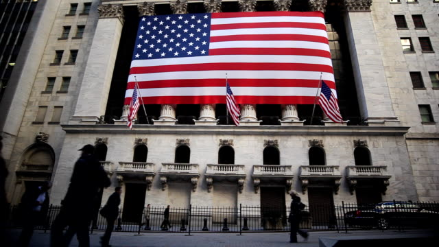 vídeos de stock, filmes e b-roll de an american flag hangs outside the new york stock exchange. - economia
