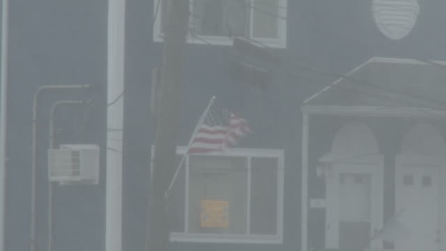 an american flag mounted to the front of a residential home flaps in high winds and torrential rain during tropical storm isaias in rockaway queens... - scott mcpartland stock videos & royalty-free footage