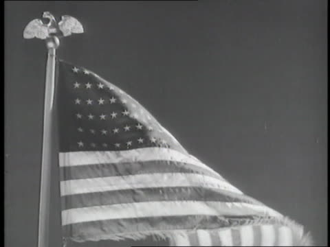 an american flag rises to the top of a flagpole on a windy day - patriotism stock videos & royalty-free footage