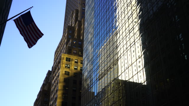 An American Flag shaking by winds among the Midtown Manhattan buildings in New York City. Building surface reflects figure of the other buildings.