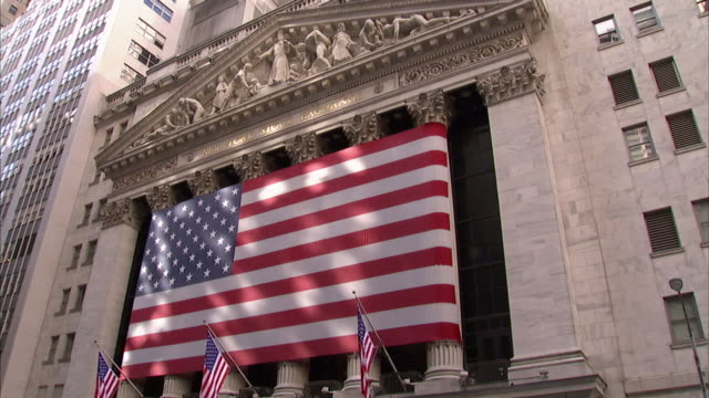 an american flag stretches across the columns of the new york stock exchange on wall street in new york city. - ペディメント点の映像素材/bロール