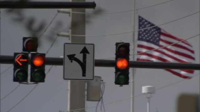 an american flag waves above traffic signals. - patriotism stock videos & royalty-free footage