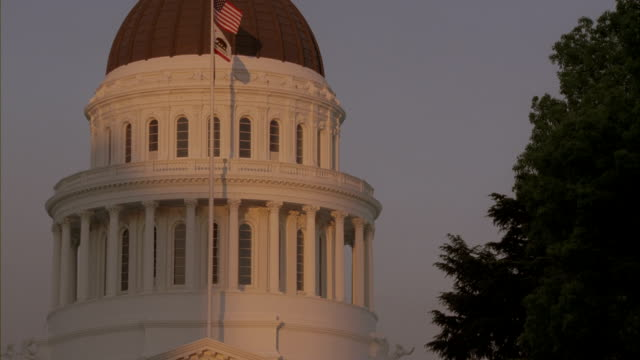 An American Flag waves in front of the California State Capitol in California.
