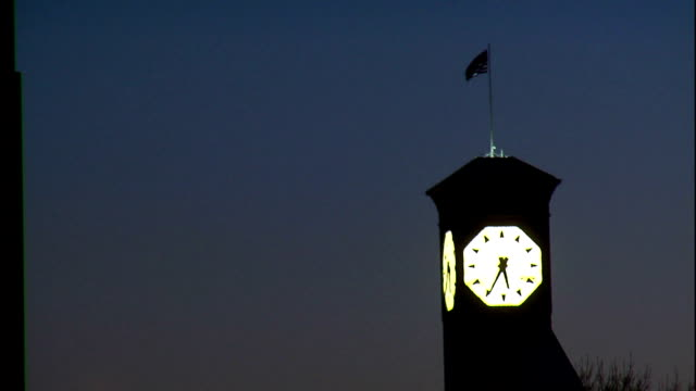 an american flag waves in the wind on top of an illuminated clock tower. - turmuhr stock-videos und b-roll-filmmaterial