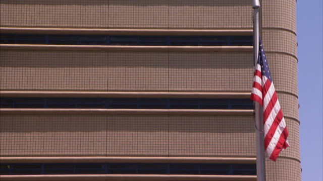 an american flag waves near the rounded corner of an office building in las vegas, nevada. - 旗棒点の映像素材/bロール