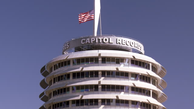 an american flag waves over the capitol records building in hollywood, california. - capitol records stock-videos und b-roll-filmmaterial