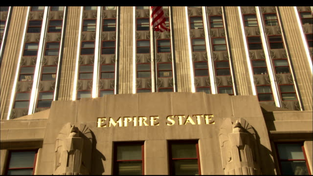 an american flags flies above the entrance of the empire state building in new york city. available in hd. - eingang stock-videos und b-roll-filmmaterial