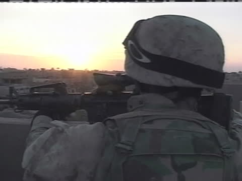 an american soldier aims his weapon over the side of a rooftop in iraq. - (war or terrorism or election or government or illness or news event or speech or politics or politician or conflict or military or extreme weather or business or economy) and not usa stock videos & royalty-free footage