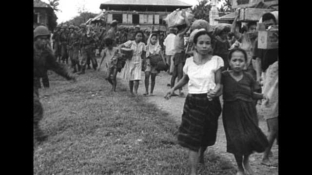 vídeos de stock, filmes e b-roll de an american soldier carries a baby and holds the hand of a small child as a crowd of filipino people carrying their belongings follows / a man rides... - filipino
