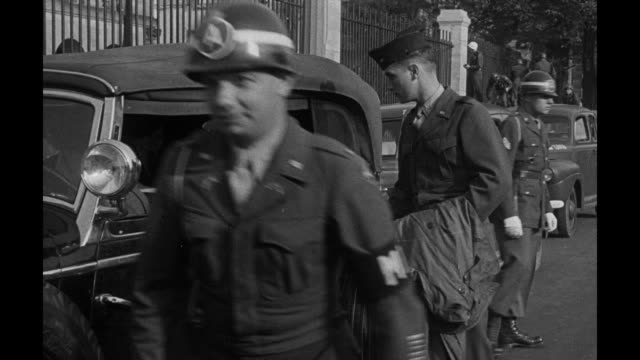 an american soldier directs light traffic on street bordered with damaged buildings and a sixwheel armored vehicle / chief us prosecutor robert h... - 1946 stock-videos und b-roll-filmmaterial