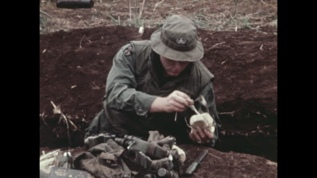 an american soldier examines and disarms hand grenades and other weapons taken from north vietnamese commandos killed in an attack. michael... - hand grenade stock videos & royalty-free footage