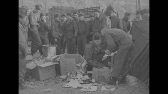 an american soldier reads a letter with open boxes on ground in front of him / assorted items on ground including butterfinger and milky way candy... - milky way stock videos & royalty-free footage