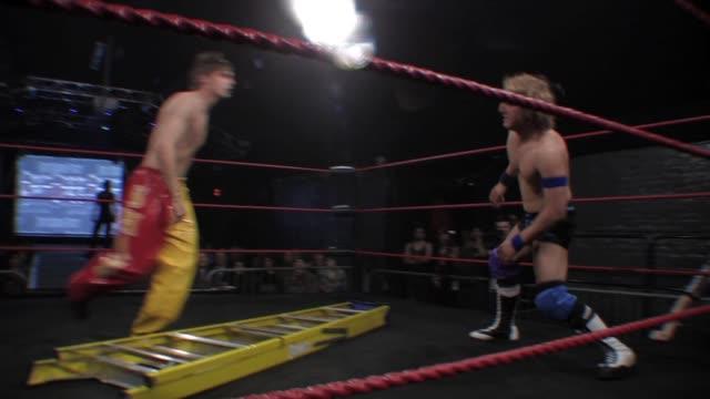 vídeos y material grabado en eventos de stock de an american style professional wrestling ladder match featuring a suplex slam onto the ladder - oficial deportivo