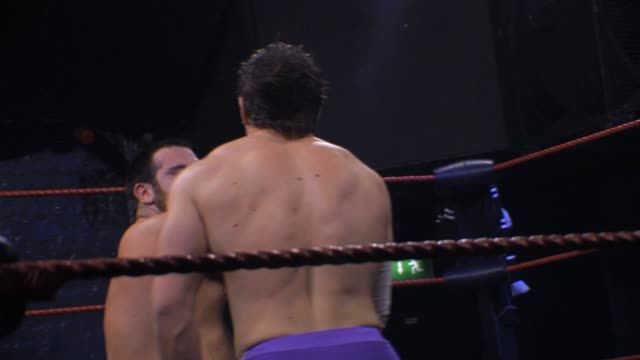 An American style professional wrestling match sequence 2 wrestlers exchanging punches slaps and chops