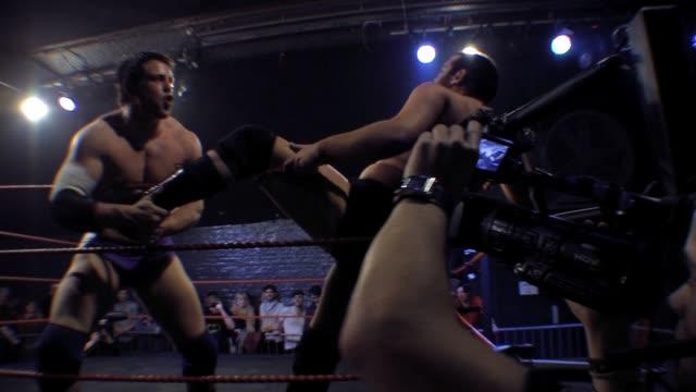vídeos y material grabado en eventos de stock de an american style professional wrestling match sequence with cameraman filming in foreground - oficial deportivo