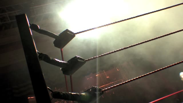 An American style professional wrestling ring corner post and ropes with smokey backdrop