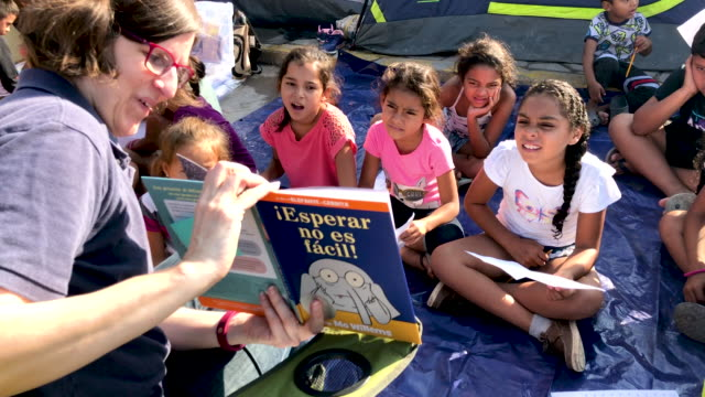 """an american volunteer reads a mo williams children's book """"waiting is not easy"""" during class at """"the sidewalk school"""" for immigrant children at a... - ボーダーズ・ブックス点の映像素材/bロール"""