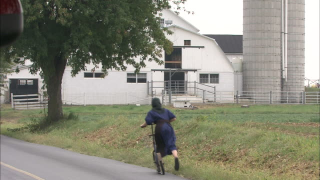An Amish girl pushes a scooter toward a farm.