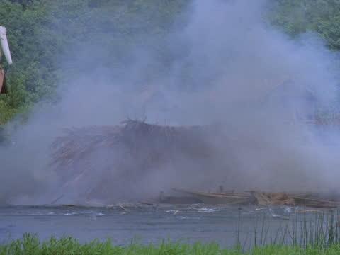 an ammo shack ignites and explodes. - 草葺小屋点の映像素材/bロール