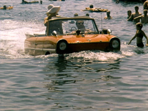 An Amphicar - amphibious car -  motoring through water and onto shore