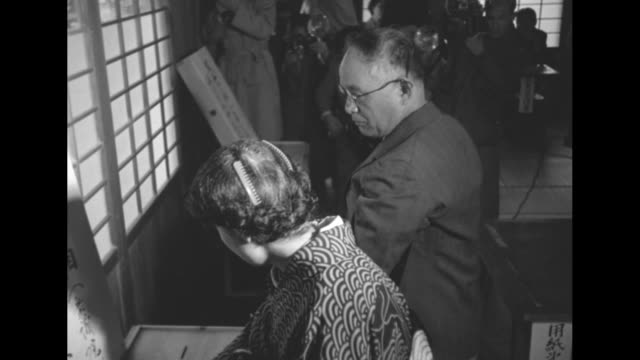 An amputee and woman check in at polling place table and others line up / the man voting at partition his crutches on either side / small baby in...