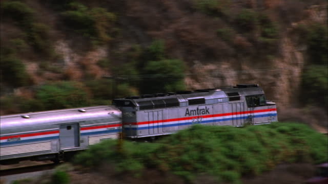 An Amtrak train travels along the coast in Ventura, California. Available in HD.
