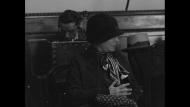 an amused alice roosevelt longworth sits in audience during senate post office committee hearing / side view older women in audience knit - 航空便点の映像素材/bロール
