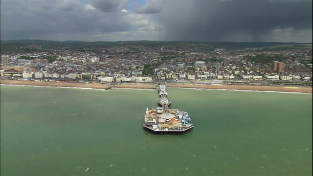 an amusement park covers the end of the palace pier in the coastal town of brighton, england. - 英国 ブライトン点の映像素材/bロール