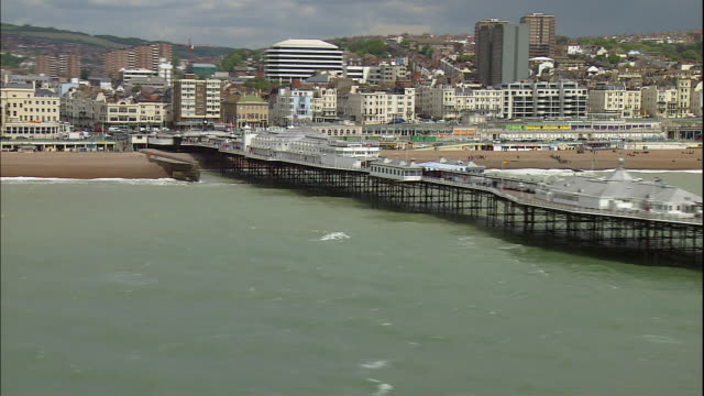 an amusement park covers the end of the palace pier in the coastal town of brighton, england. - ブライトン パレスピア点の映像素材/bロール