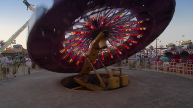 vídeos y material grabado en eventos de stock de an amusement park ride spins with others in operation behind it.  families are having fun at a resort town on the jersey shore - bulevar