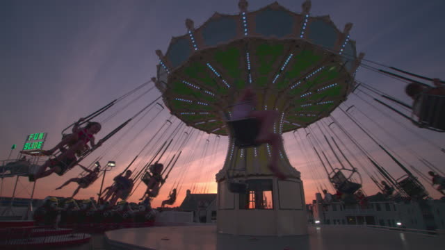 an amusement park swing ride in ocean city nj at sunset. - 回転遊具点の映像素材/bロール