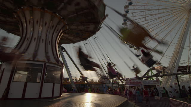 An amusement park swing twirls in the sunset as a Ferris wheel rotates behind.  Families are having fun at a resort town on the Jersey Shore