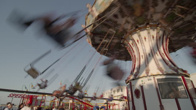 An amusement park swing twirls with a group of happy children.  Families are having fun at a resort town on the Jersey Shore