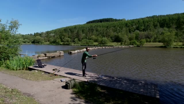 an angler casts from hissed from a fishing platform, restrictions on fishing in wales differs to the in england may 29, 2020 in deri, wales, united... - village stock videos & royalty-free footage