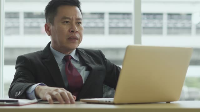 an angry asian businessman at his workplace - frustration asian failure stock videos & royalty-free footage