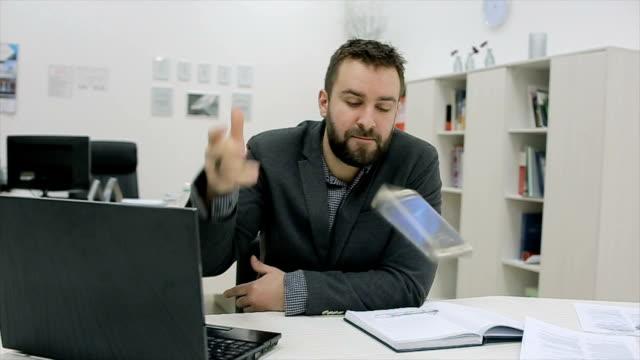vidéos et rushes de un homme en colère lance un téléphone - folie