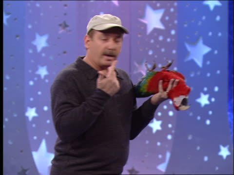 an animal trainer holds a parrot upside down, counts, and then flips the parrot right side up. - televisione a ultra alta definizione video stock e b–roll